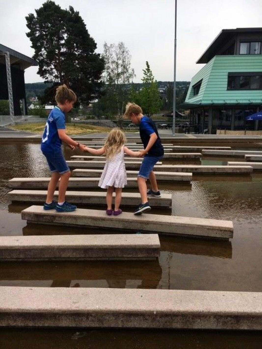 Simon, Leo og Jenny i vannspeilet foran Sentrum videregående skole.