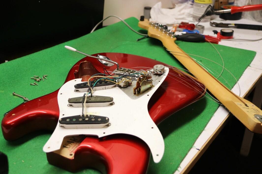 Lasse har mange prosjekter på gang, akkurat nå holder han på å datere en gammel gitar på reparasjonsverkstedet. Ellers går det mye i å reparere gitarer med blant annet knekt hals, da må det limes, tvinges og lakkeres for å få det pent igjen.