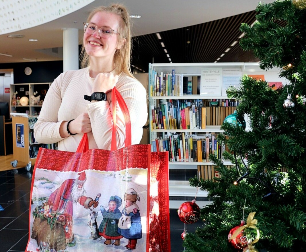Linda Andersen Ness viser frem adventsposene med 24 utlånte bøker og et julepyntet bibliotek.