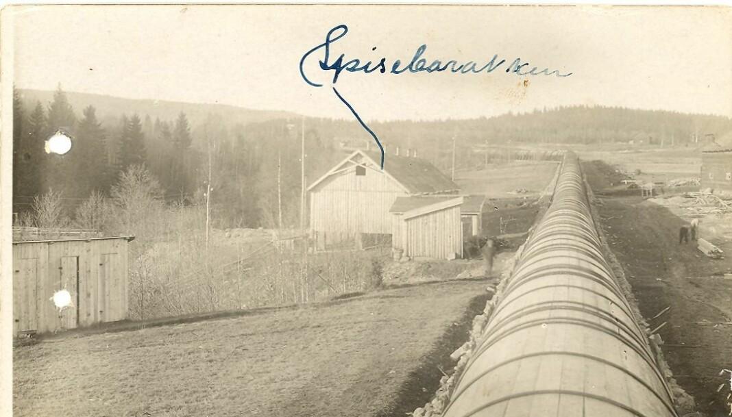 Den nesten 1200 meter lange rørgaten ble hovedsakelig bygget i tre. Mange arbeidere var involvert og huset til venstre i bildet var en spisebarakk som også noen har skrevet på dette gamle bildet.