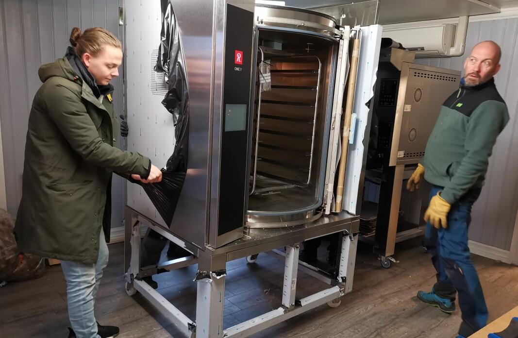 Endelig står den nye ovnen der. 400 kilo er løftet opp på stativet. Nå gjenstår de siste tilkoblingene.