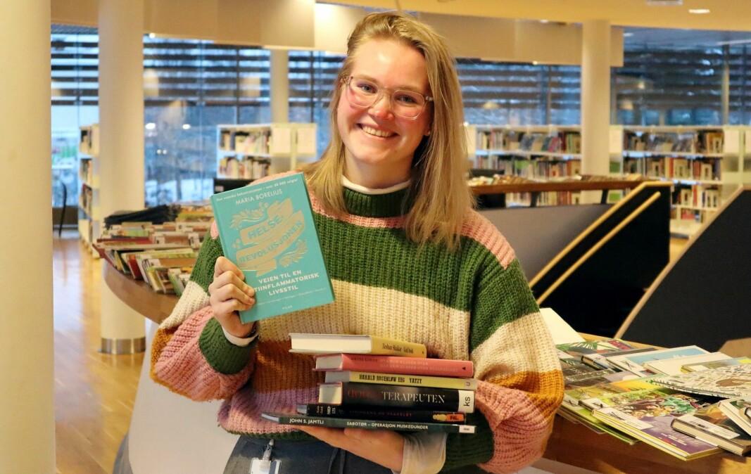 Bibliotekar Linda Andersen Ness med noen av fjorårets mest lånte bøker på Kongsvinger bibliotek
