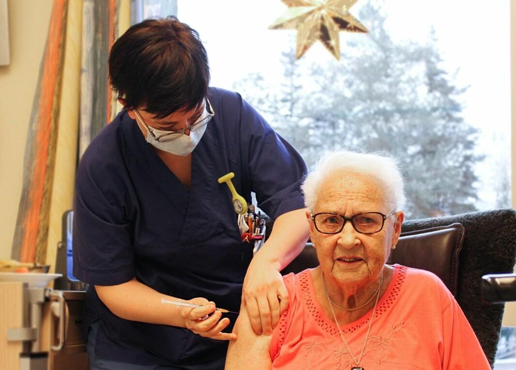 Sykepleier Lynn Marion Hole setter vaksinen på Thora Marit Jacobsen. Pasientene blir vaksinert på rommene sine, i trygge og rolige omgivelser sammen med sykepleiere de kjenner godt.