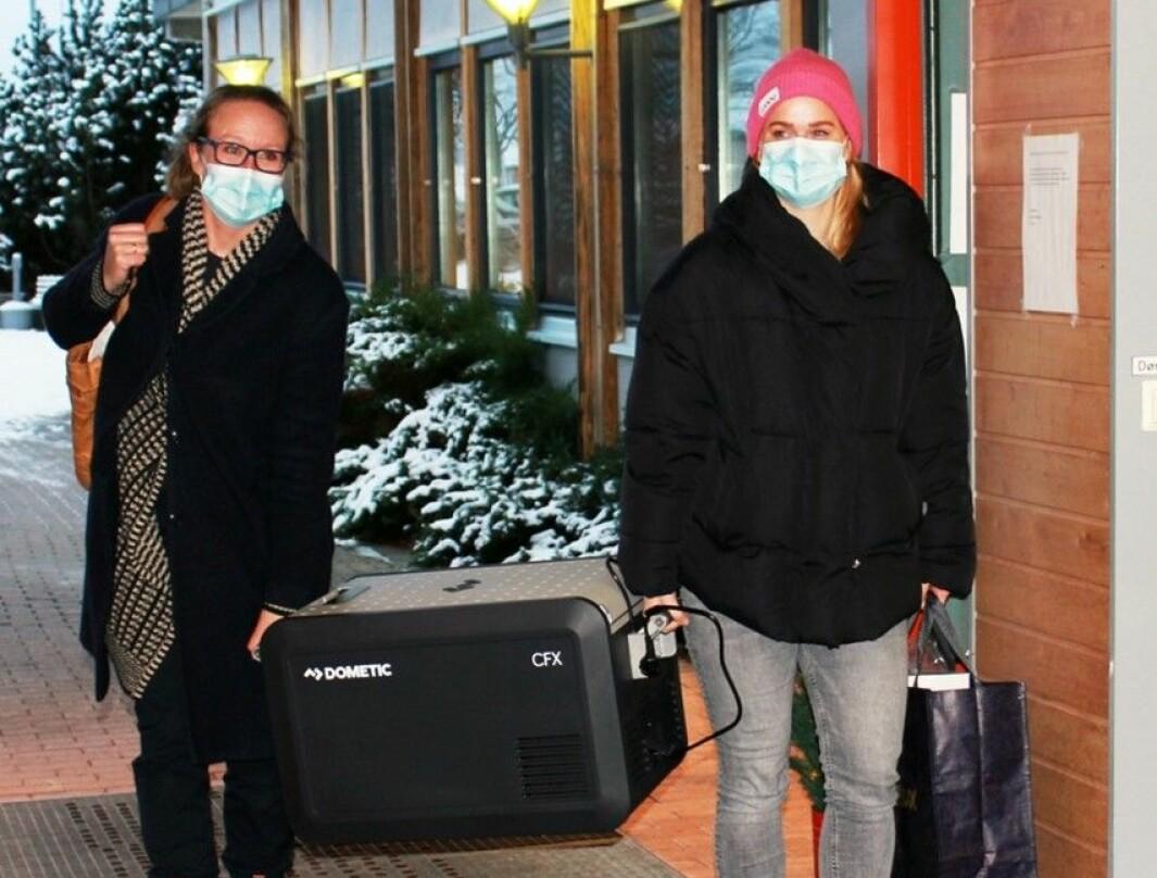 Kommuneoverlege Camilla Kvalø Smedtorp (til venstre) og vaksinekoordinator Linda Langfoss Utgård ankommer Langelandhjemmet med vaksinene trygt oppbevart i kjøleboks.