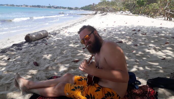 Raymond hadde god tid i utlandet. Her prøver han å lære ukulele på en strand i Columbia.
