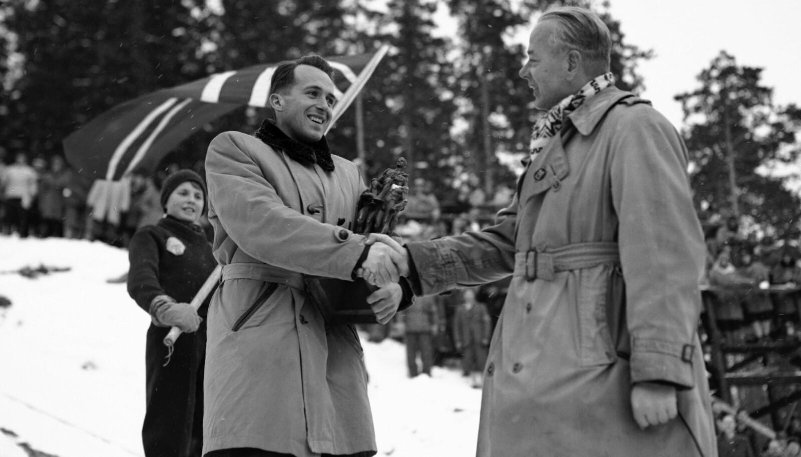 Hallgeir Brenden (t.v.) mottar Egebergs Ærespris på kulen etter 1. omgang av hopprennet i NM i 1954. Det er Arthur Ruud som overrakte prisen. I bakgrunnen en lokal flaggbærer.
