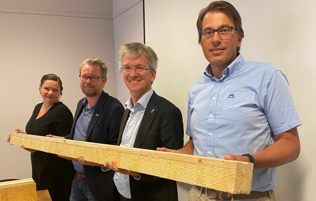 Direktør Erik Nilsen (t.h) og ordfører Margreth Haarr kunne fortelle Statssekretærene Paul Schaffey (t.h) og Raymond Robertsen om et nytt treprodukt for byggeindustrien utviklet der skogen faktisk vokser.